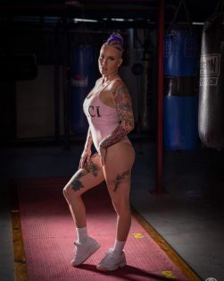 Bec Rawlings posing whilst wearing a pink one-piece