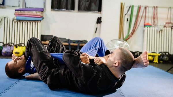 BJJ practitioners practicing an armbar submission.