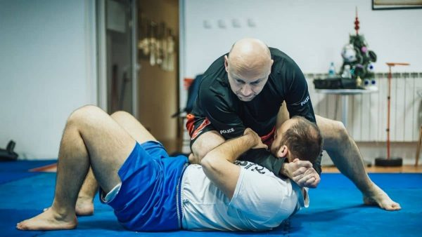 MMA students practicing a neck crank on the mat
