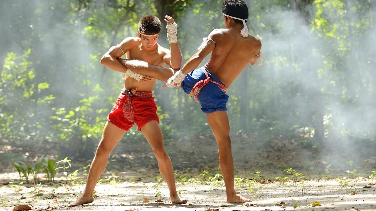 Muay Thai fighters practicing kicks outdoors