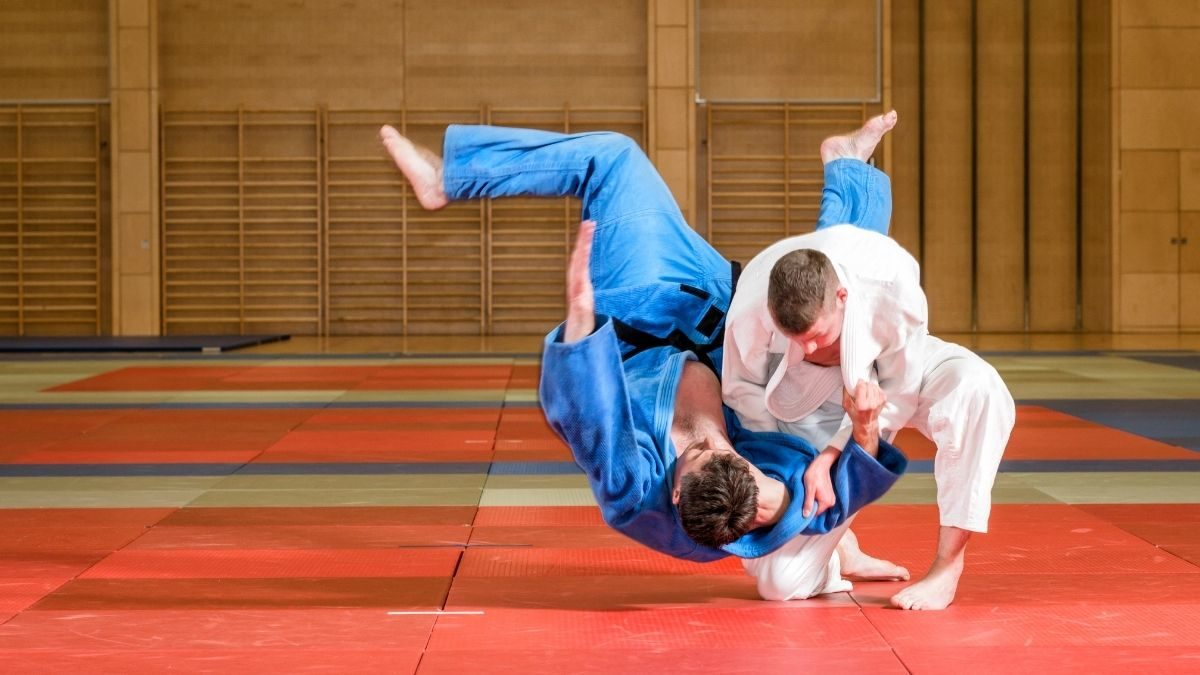 One Judo competitor throwing the other using Ippon Seoi Nage